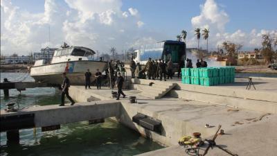 Personal de ShelterBox y el Programa Mundial de Alimentos de las Naciones Unidas descargan un cargamento de suministros de ShelterBox en la bahía de Les Cayes en Haiti. Las tiendas se utilizarán para ayudar a los profesionales médidos a detectar y tratar a las víctimas del cólera. Fotografía de: Alexis Masciarelli